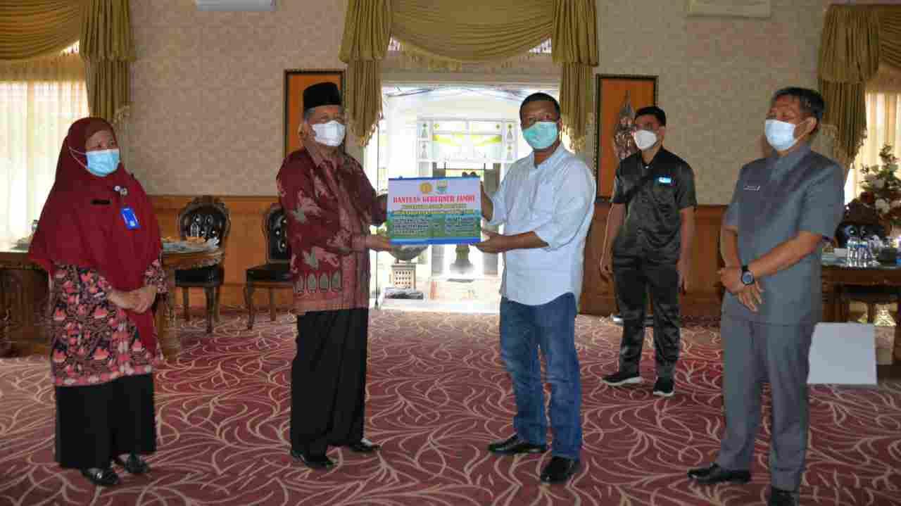 Abdullah Sani saat serahkan bantuan yang diterima oleh Romi Hariyanto